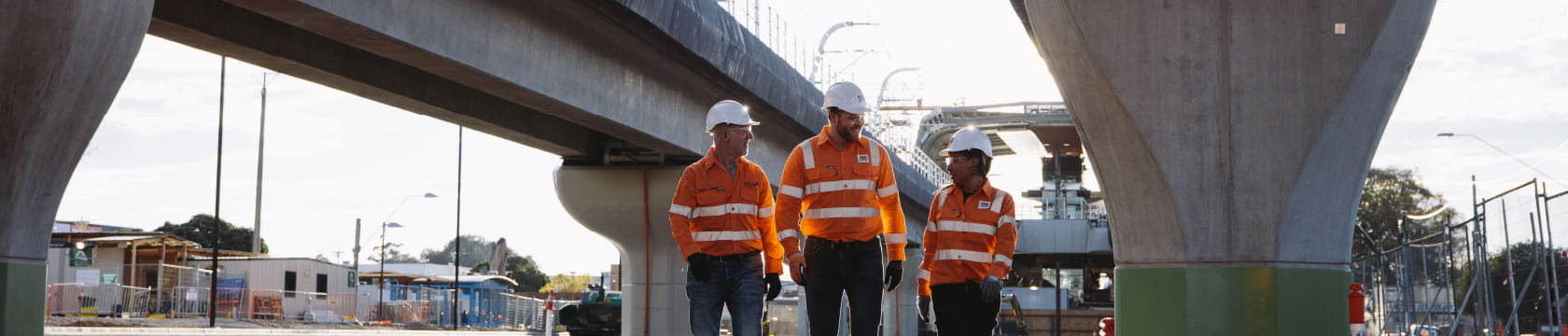 3 workers walking under rail bridge