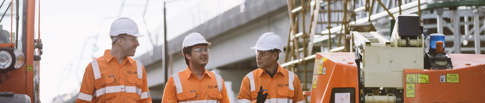 3 male workers walking and talking on site with bridge in background