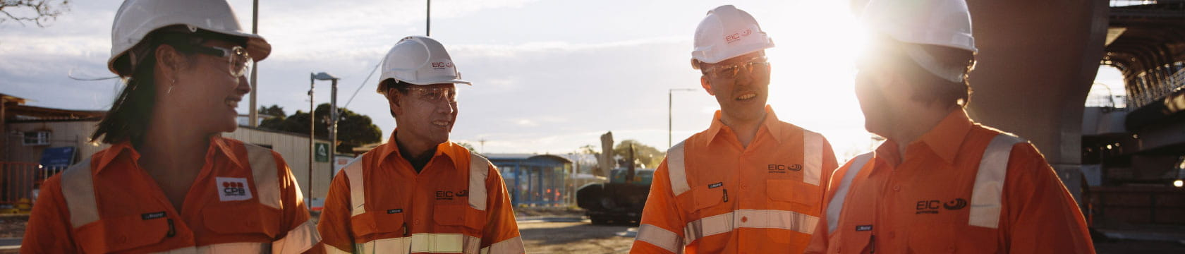 1 female and 3 male workers talking with sunsetting in background