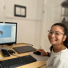 Female graduate smiling at desk in front of 3D model on computer