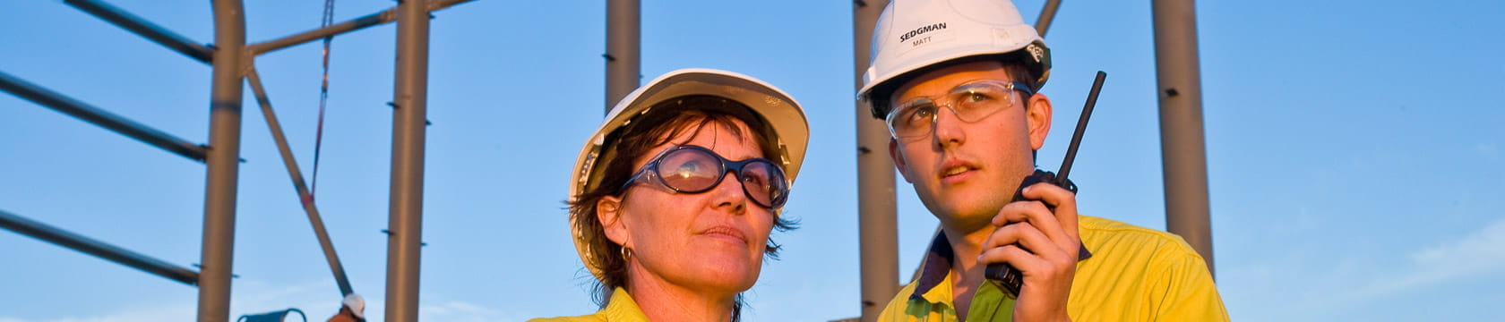 a woman and a man in front of mineral processing infrastructure